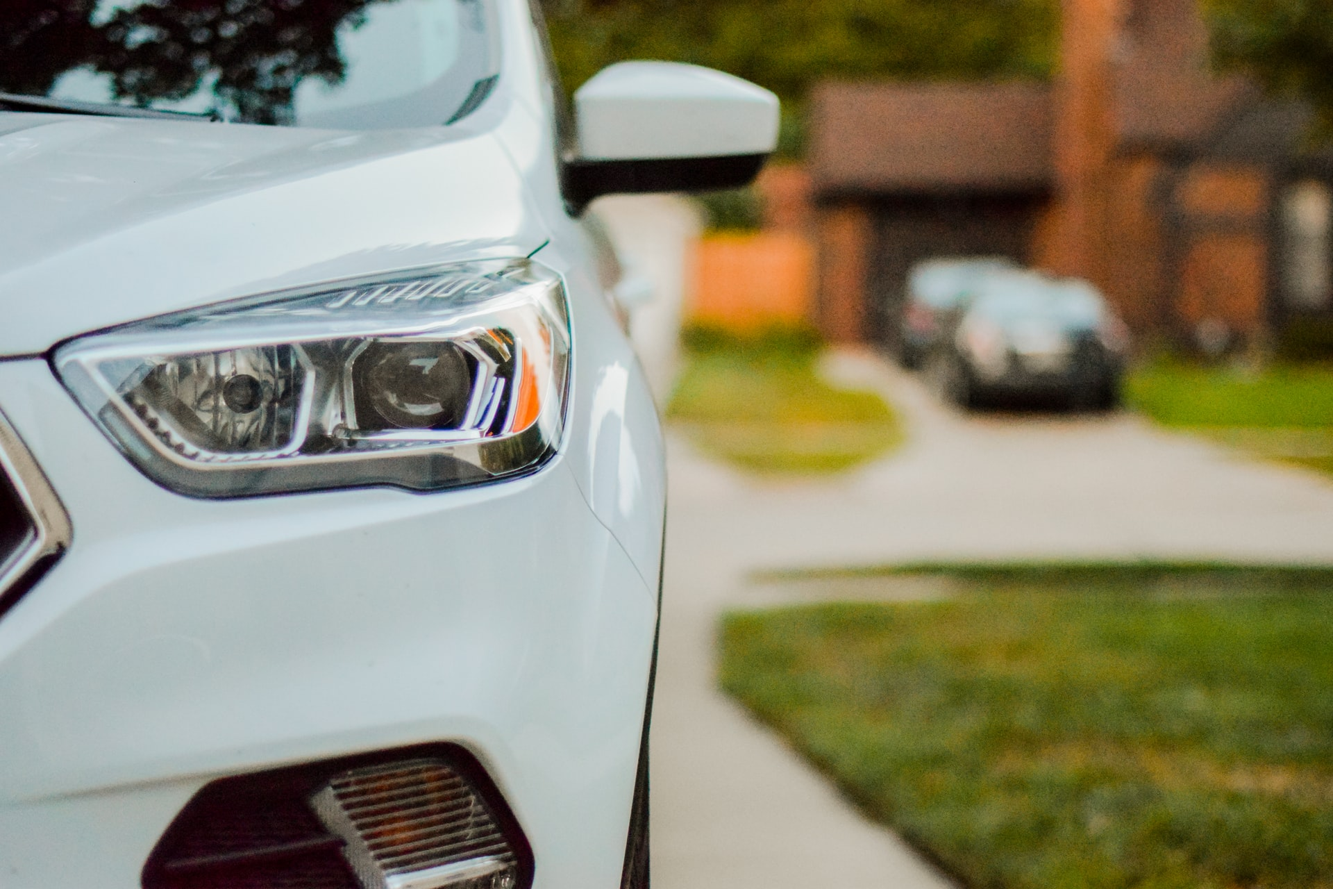 closeup of white car in driveway for auto reform concept