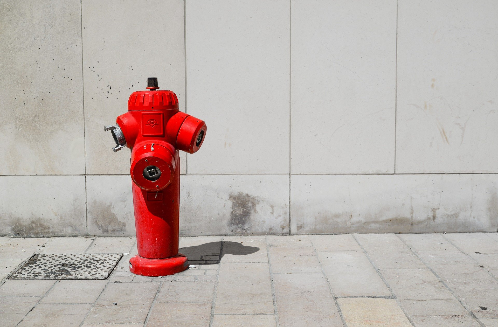 red fire hydrant on sidewalk for fire safety