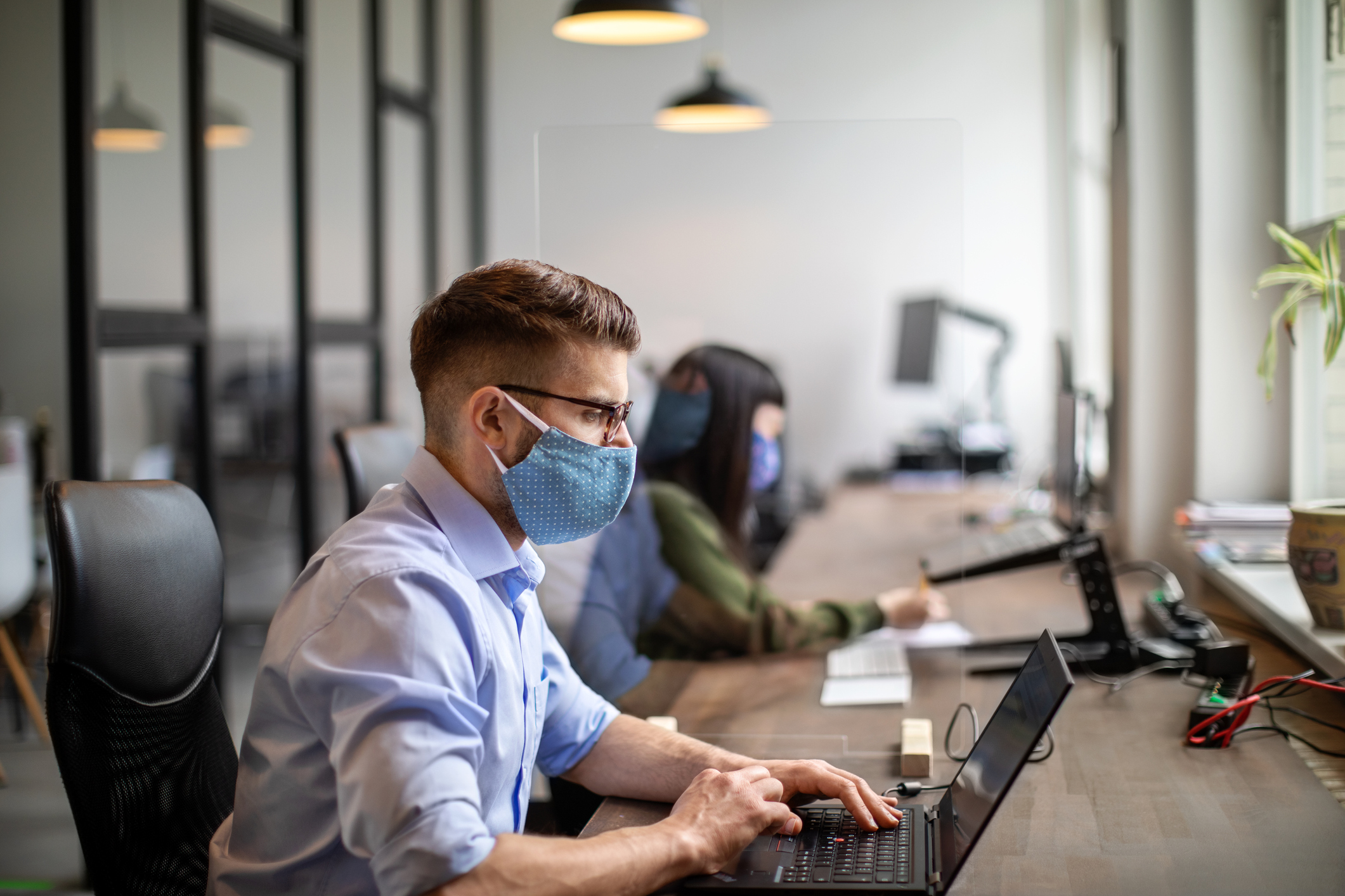 man and woman sitting at desk with masks on in the workplace
