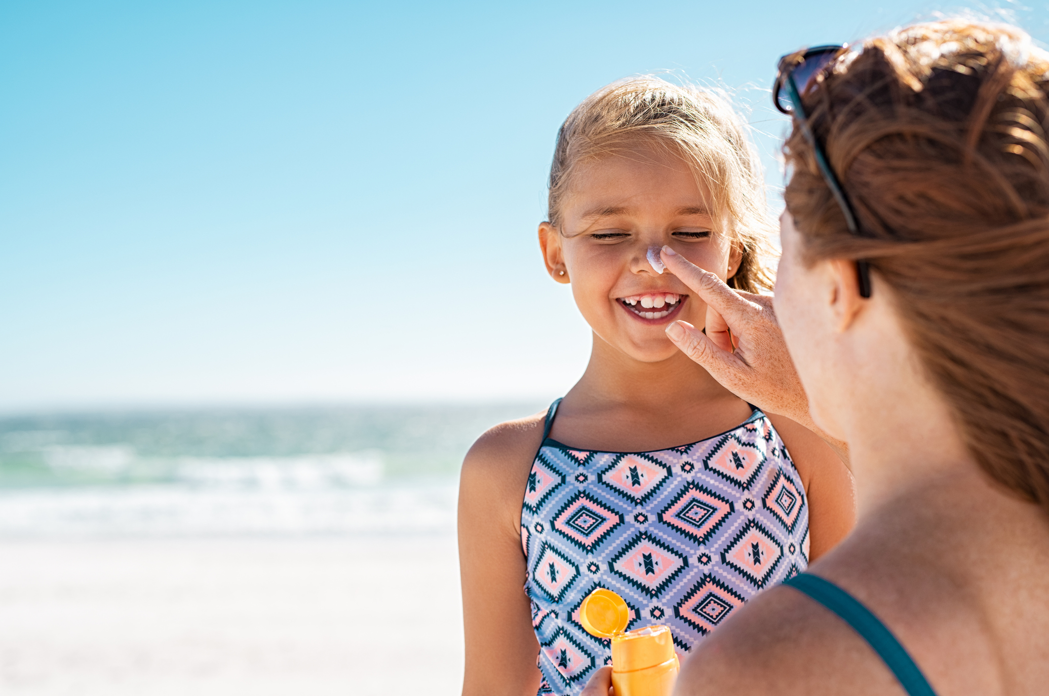 mother applying suntan lotion to daughter's face to stay safe in heat